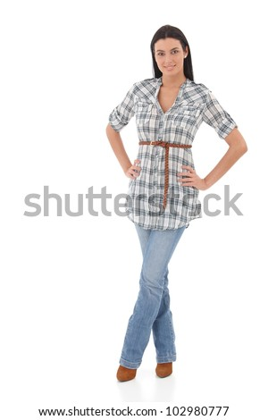 Pretty girl standing over white background, wearing jeans and shirt, smiling.