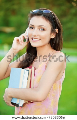 pretty girl-student holds a book and talking on a cell phone on the natural background