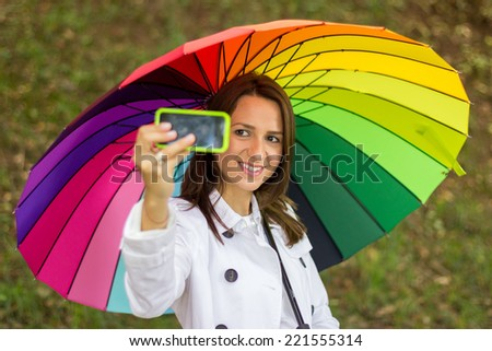 pretty girl take a self portrait with her smart phone in park under colorful umbrella - stock photo