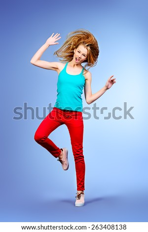 Pretty girl teenager jumping at studio expressing happiness.  - stock photo