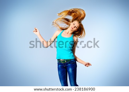 Pretty girl teenager jumping at studio expressing happiness. Hair care, healthy hair. - stock photo