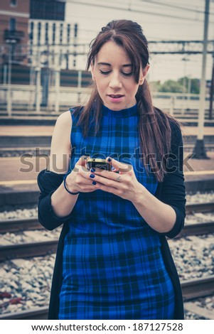 Pretty girl texting on phone along the tracks in a railroad station