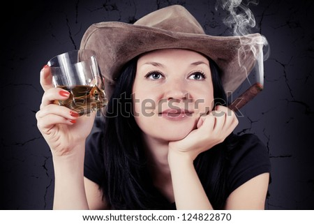 pretty girl the cowboy with a cigar and whiskey - stock photo