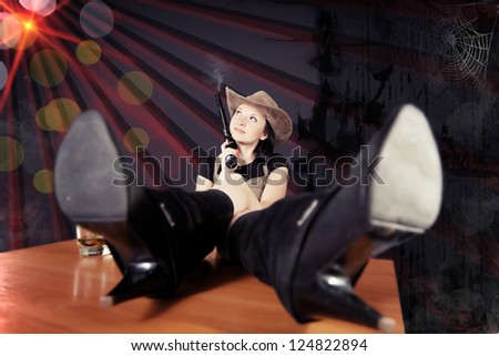 pretty girl the cowboy with a gun on a dark background - stock photo