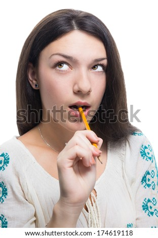 Pretty girl thinking with a pen in mouth, isolated on white.