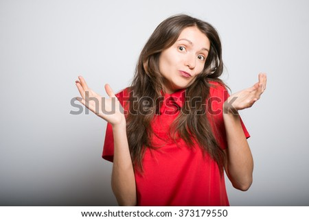 pretty girl throws up his hands in a red dress, studio, isolated - stock photo