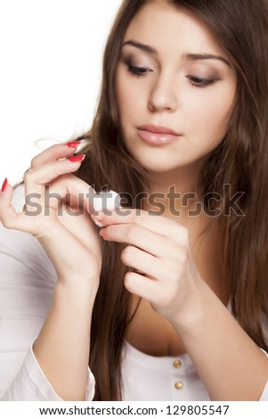 pretty girl using a cotton to removes her nail polish from her nails