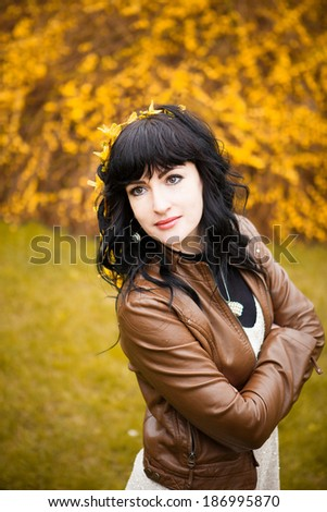 Pretty girl walking in the garden in spring. portrait brunette girl on a background of yellow flowers.