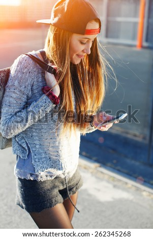 Pretty girl walking outdoors in the street while using busy a smart phone, gorgeous young woman wearing casual spring clothes walking down a city street while typing on her cell phone, flare sun - stock photo