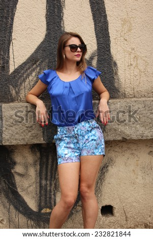Pretty girl wearing a blue dress on the wall - stock photo