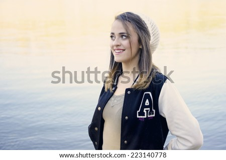 Pretty girl wearing a school varsity jacket in front of the reflection of a slow moving river - stock photo