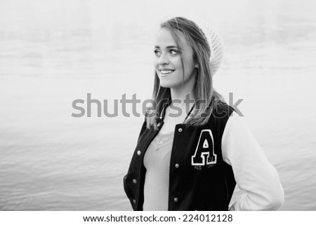 Pretty girl wearing a school varsity jacket in front of the reflection of a slow moving river in black and white - stock photo