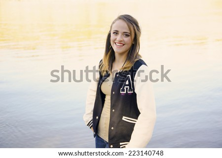 Pretty girl wearing jeans and a school varsity jacket in front of the reflection of a slow moving river - stock photo