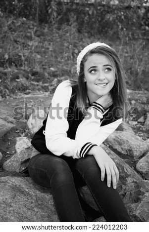 Pretty girl wearing jeans and a varsity jacket sitting on river rocks in black and white