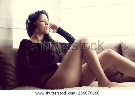 pretty girl wearing panties plus sexy top sitting in sofa with headphones and enjoys music eyes closed