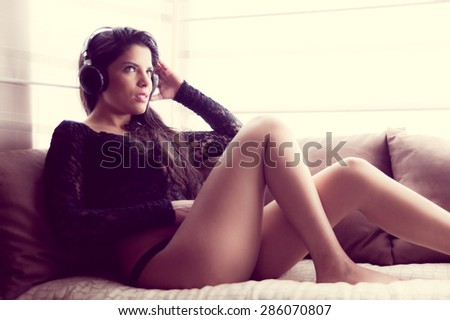 pretty girl wearing panties plus sexy top sitting in sofa with headphones and focused facial expression