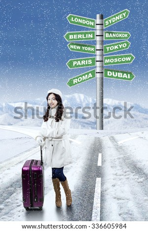 Pretty girl wearing winter coat, standing on the road with luggage and singpost of winter destination vacation choices