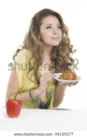 Pretty girl with a croissant and a paprika, deciding what to take - stock photo