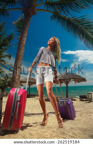 Pretty girl with a suitcases and on a resort - stock photo