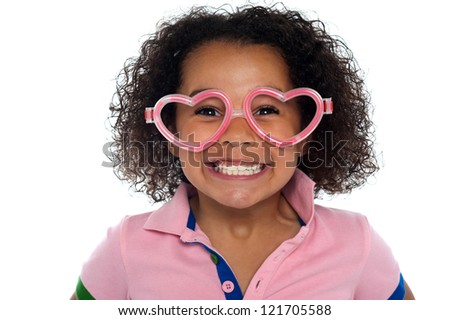 Pretty girl with a wide grin looking through heart shaped frame. - stock photo