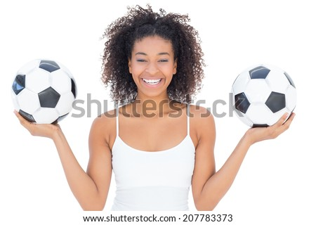Pretty girl with afro hairstyle smiling at camera holding footballs on white background