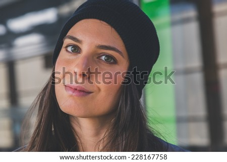 Pretty girl with beanie posing in a metro station