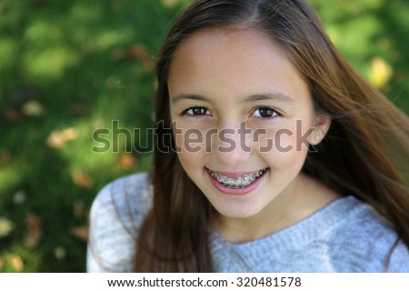pretty girl with big brown eyes, long brown hair with braces - stock photo