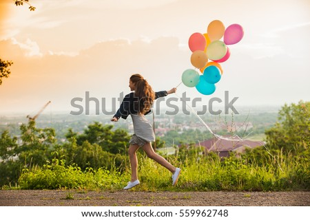 Pretty girl with big colorful balloons walking on the hills near the town