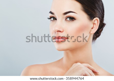 Pretty girl with big eyes and dark eyebrows, with naked shoulders, looking at camera and smiling, a model with light nude make-up, gray studio background, beauty photo, copy space, close up. - stock photo