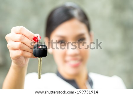 Pretty girl with car key in her hand - stock photo