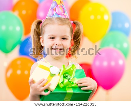 pretty girl  with colorful balloons and gifts on birthday party