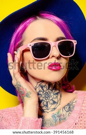 Pretty girl with crimson hair wearing bright clothes and sunglasses posing over yellow background. Bright style, fashion. Optics style. Tattoo. - stock photo