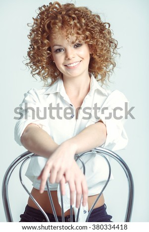 Pretty Girl with Curly Blonde Hair and Toothy Smile. Attractive Young Woman Sitting On Chair. - stock photo