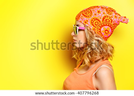 Pretty girl with curly blonde hair wearing bright clothes and sunglasses posing over yellow background. Bright style, fashion.  - stock photo