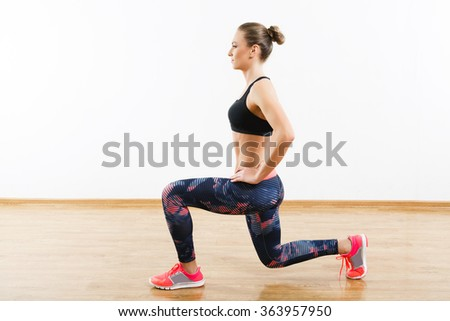 Pretty girl with dark hair wearing pink snickers, dark leggings and black short top doing lunge at gym, fitness, white wall and wooden floor, copy space. - stock photo
