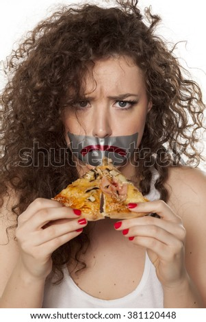 pretty girl with duct tape over her mouth, holding a piece of pizza - stock photo