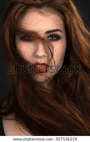 pretty girl with fluffy hair on black background