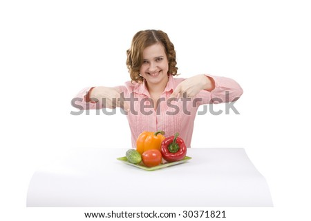 Pretty girl with fresh vegetables. Woman wants to eat fresh vegetables. Housewife is holding the plate with pepper, tomato, cucumber. Isolated over white background. - stock photo