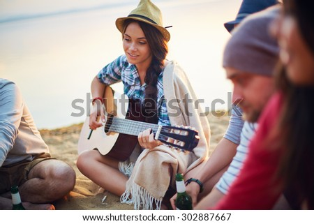 Pretty girl with guitar sitting on sandy beach among her friends