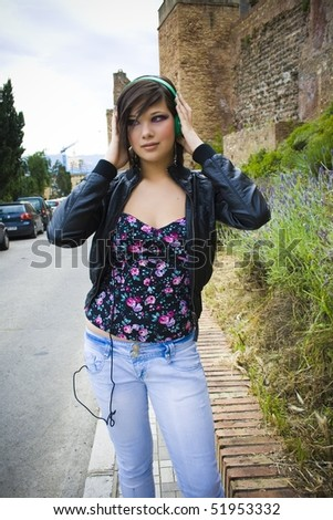 pretty girl with hands on their green headphones - stock photo