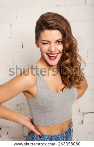 Pretty girl with healthy skin winks at the camera. White brick wall not isolated - stock photo