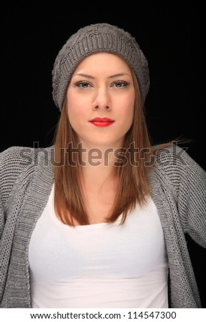 pretty girl with knit grey cap on a black background