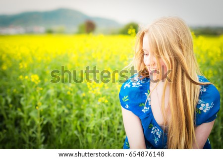 pretty girl with long blond hair in yellow canola field