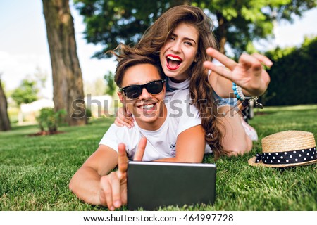 Pretty girl with long curly hair and red lips is lying on back of handsome guy in sunglasses on grass in summer park. They have fun and smile to camera.