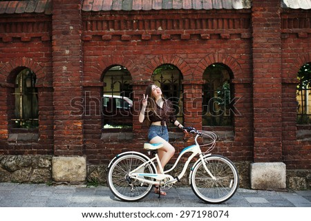 Pretty girl with long fair hair wearing on dark blouse and blue shorts with bicycle have fun on the brick wall background, on the old city street - stock photo