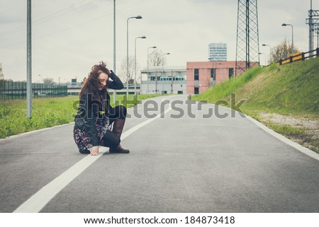 Pretty girl with long hair and black leather jacket posing in the street