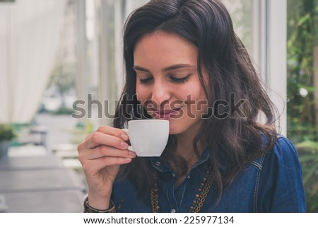 Pretty girl with long hair drinking a cup of coffee - stock photo