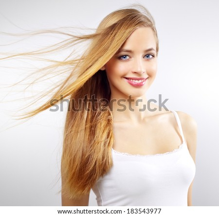 Pretty girl with long hair on a gray background