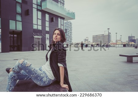 Pretty girl with long hair poses in the city streets
