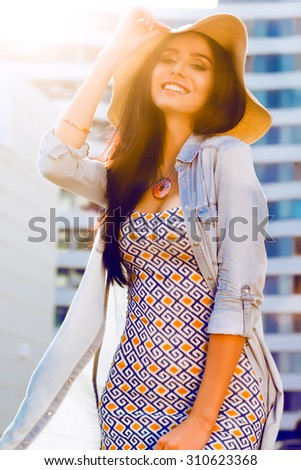 Pretty girl with long hairs and pretty smile on the street. Fashion details, floral dress. stylish jewelry, toned colors, street style. warm toned colors. making selfie, having fun.smiling woman - stock photo
